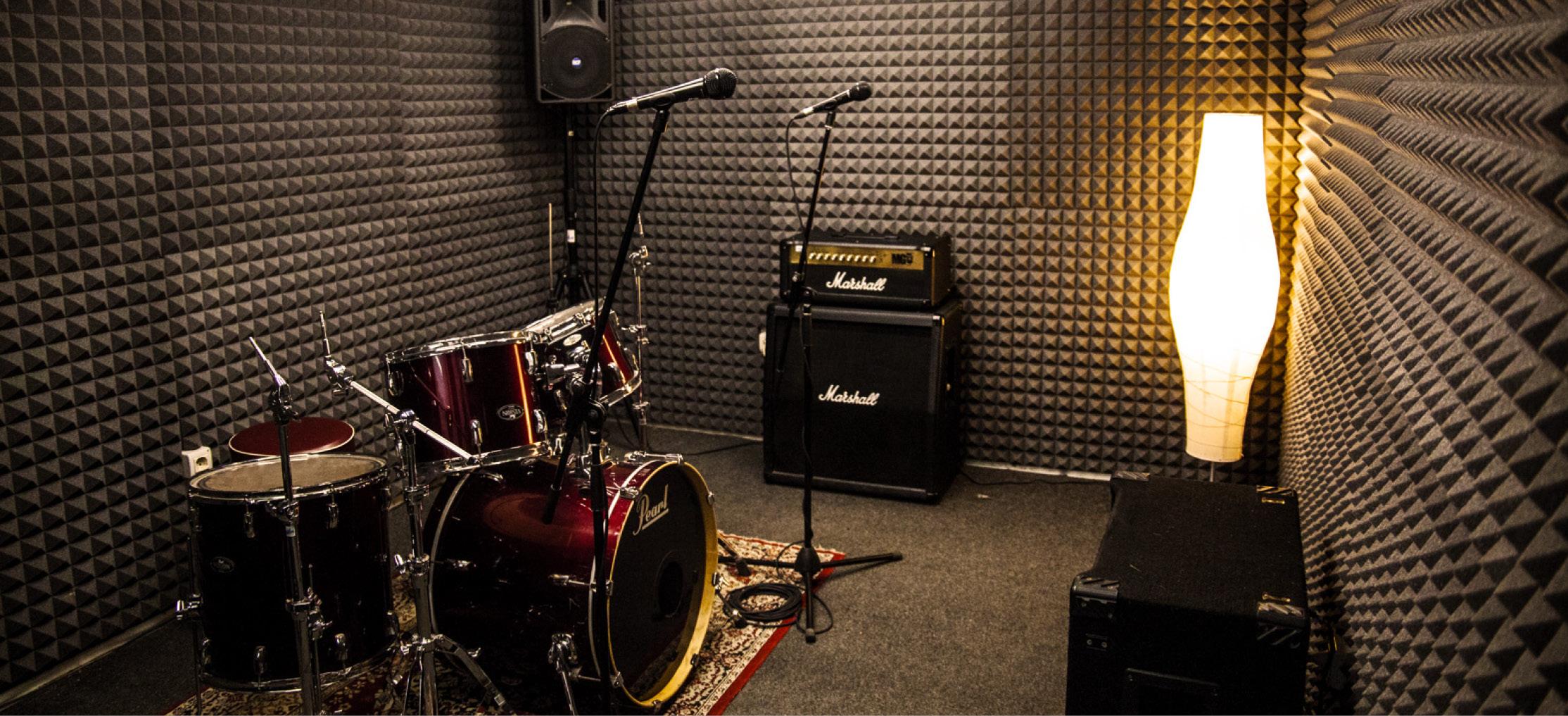 Foto di batteria, microfoni, amplificatore chitarra e basso nella sala 4